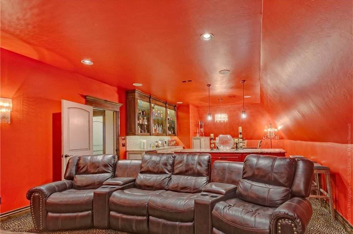 Brown leather recliners, glass-front cabinets, an island bar, and ambient lights completed the media room.