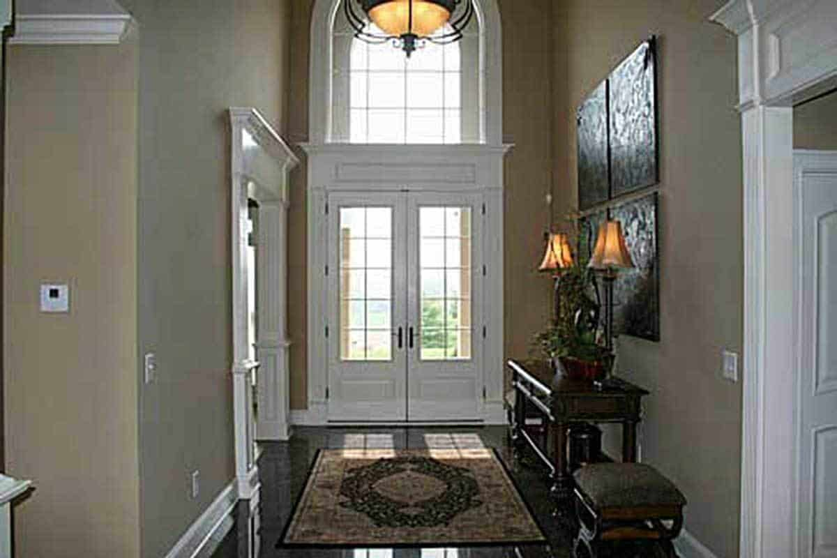 The foyer has a white french door, a classic area rug, and a dark wood console table flanked by cushioned stools.