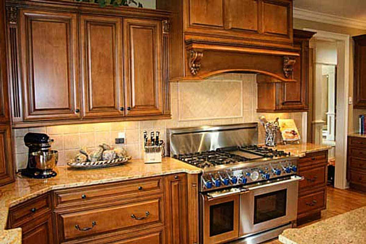 A closer look at the cooking range nestled in between the wooden cabinets and granite countertops.