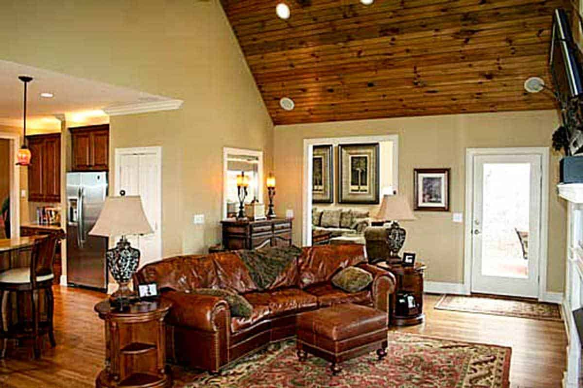 The family room has a high cathedral ceiling and natural hardwood flooring topped by a red printed rug.