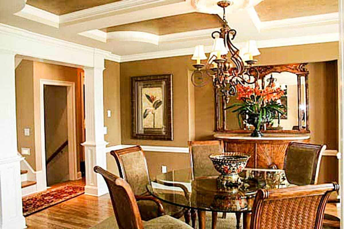 The formal dining room offers a buffet bar and a round dining set under the ornate chandelier hanging from the stylish tray ceiling.