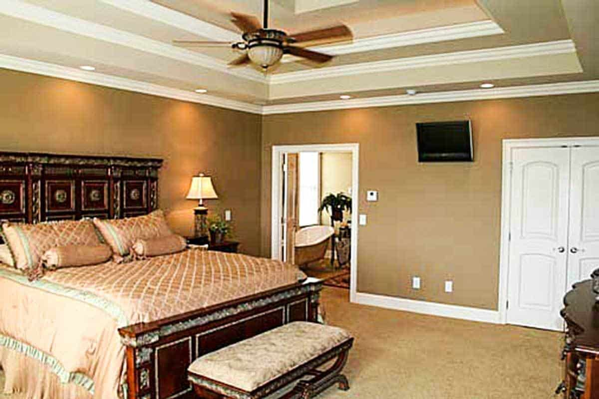 The primary bedroom has a stunning step ceiling and brown walls that blend in with the carpet flooring.