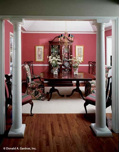 The dining room has tray ceiling, red walls, and white columns.