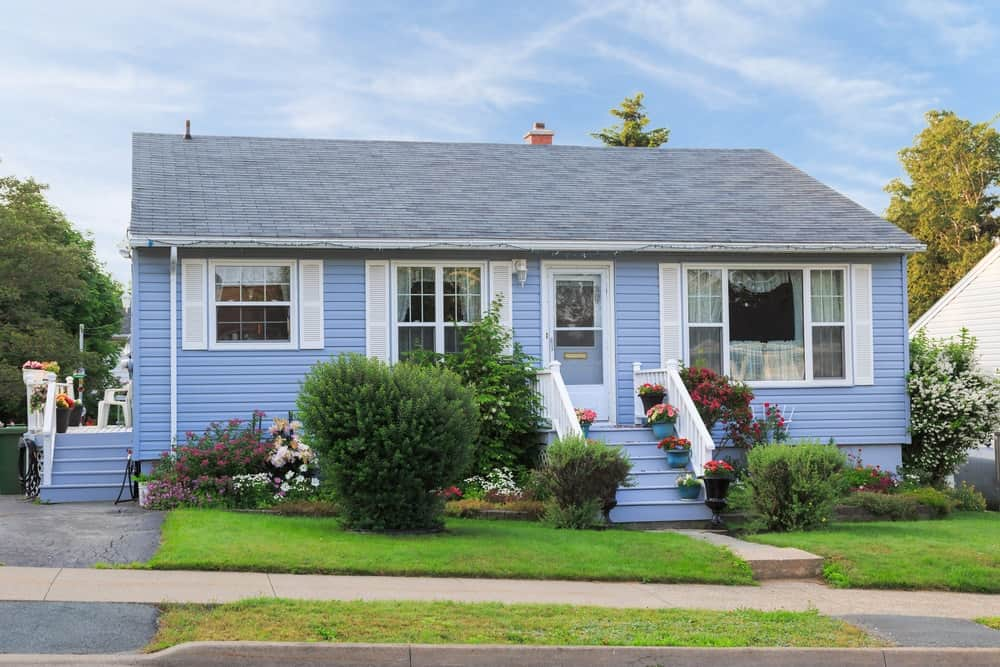 Street view of a 60s bungalow house with blue exterior siding.