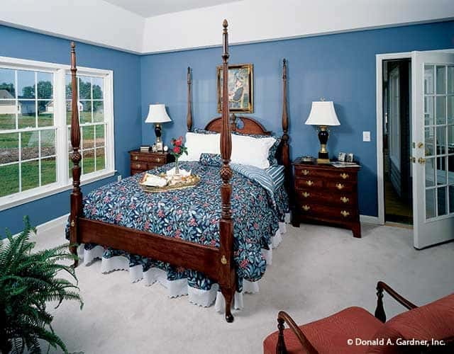 Bedroom with blue walls and four poster bed.