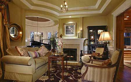 Living room with stepped ceiling, chandelier, a fireplace, and a grand piano by the bay window topped by a dome ceiling with chandelier.