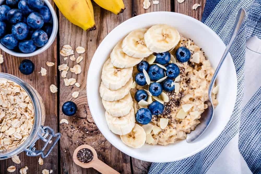 A power-packed bowl of breakfast oatmeal topped with sliced banana, berries, nuts, and chia seeds.