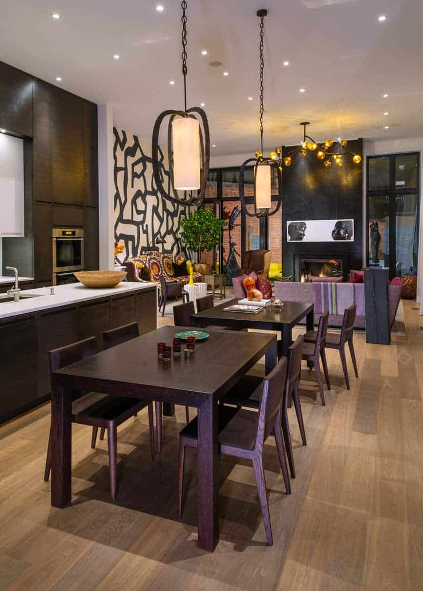 The modern kitchen features two dining tables in the open concept area and the black and white accent wall in the living room area.