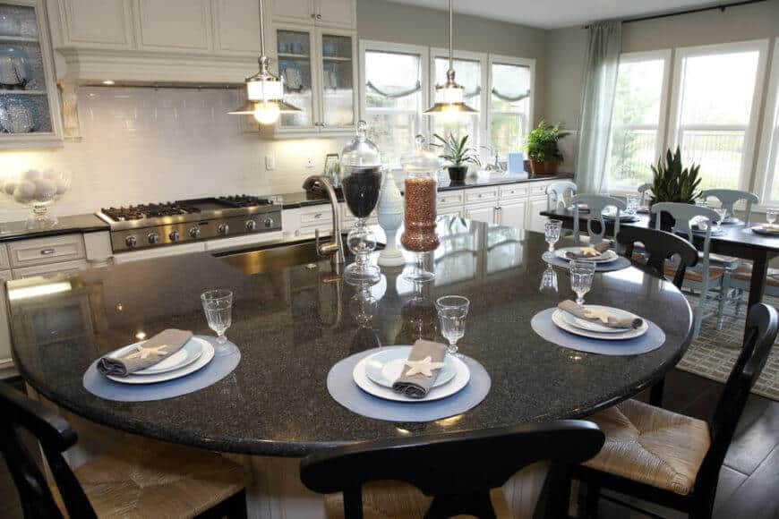 The island is a massive semi-circle design, with large basin sink on the flat end and a large curved space for in-kitchen dining. Dark dining table with a white chair on the rug.