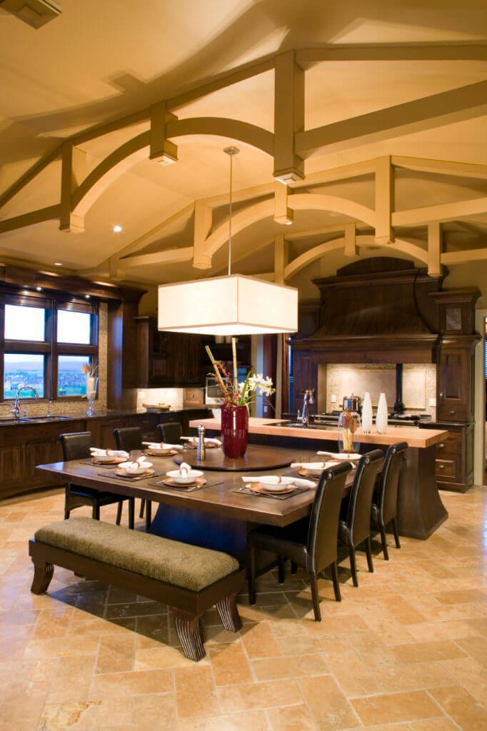 This kitchen shares with dining area. The dining area has a massive dine-in-kitchen with a beam ceiling, large pendant lighting, and tile flooring.
