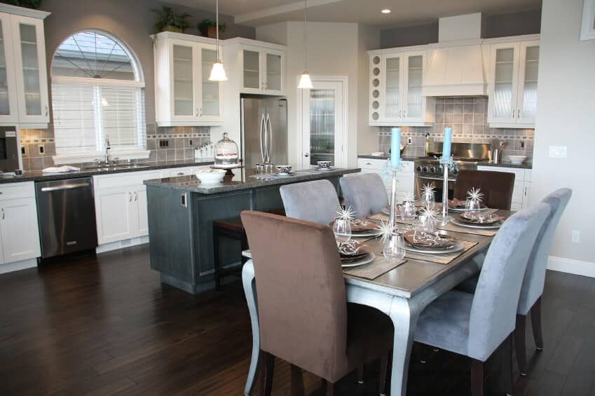 This dining area features an island kitchen with pendant lighting, white recessed panel cabinetry, and stainless steel appliances.