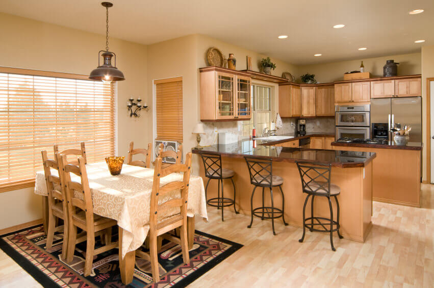 Pale wood floors mix in with the impartial dividers and permit the warm wood of the cabinets and coordinating eating furniture to become the overwhelming focus in this broad kitchen.