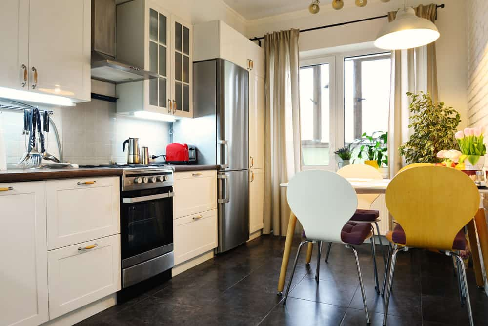 The dining area directly in the kitchen space so it's very efficient and also looks great and a single wall contemporary kitchen with white cabinetry.