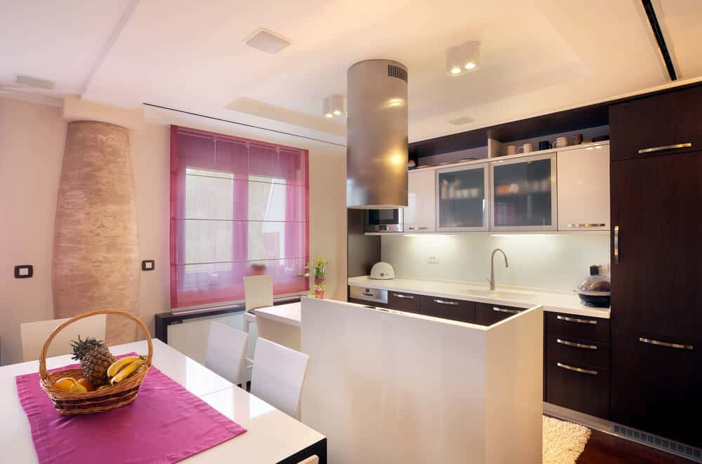 This kitchen with an island and a small dining table seating for four. This area is brightened by recessed ceiling lights.