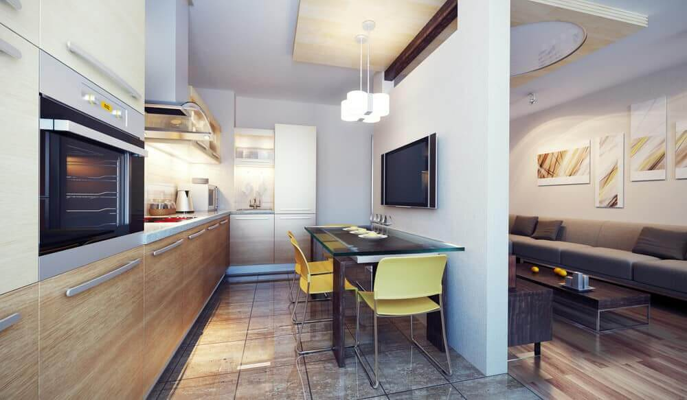 Small kitchen with a rectangular glass dining table with yellow chairs and a TV mounted on the white walls.