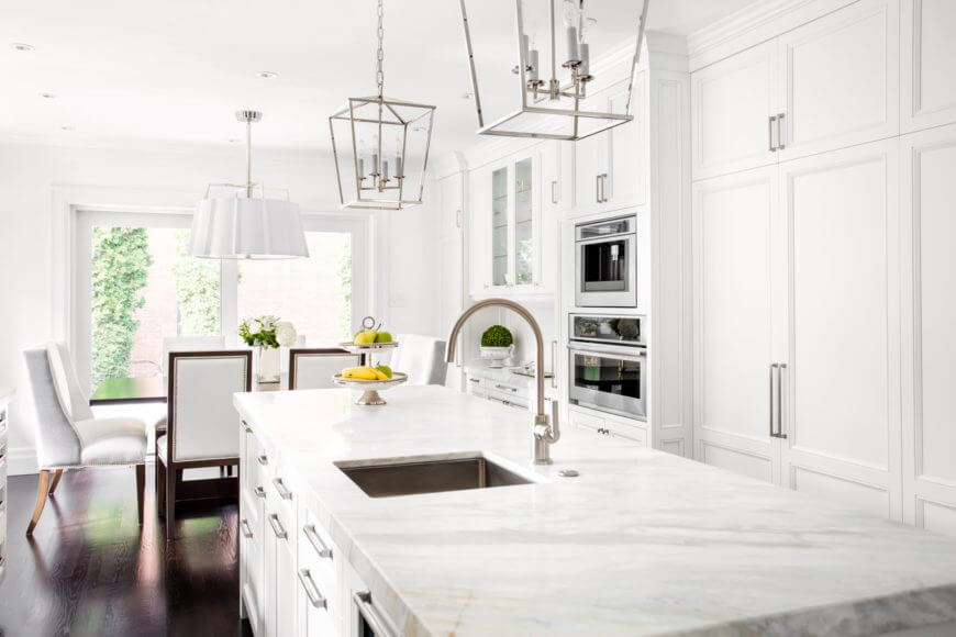 This kitchen features an elegant kitchen dining table and white chairs that fit inside this large l-shaped white kitchen.
