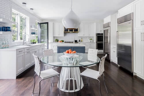 This kitchen with circular dining table paired with white chairs on the hardwood flooring and white cabinets that match the white walls and ceiling.