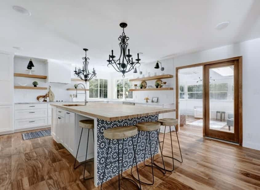 The kitchen features floating shelves and the island's enriching base underneath the wooden countertop catches attention in this kitchen.