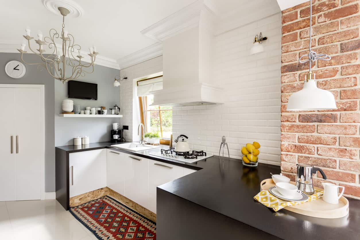 Dazzling white and a dark little kitchen with white divider close to a brick wall. Black countertops balance pleasantly with white organizer faces.