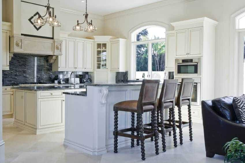 White kitchen highlights double island a customary model including a sink and dark marble countertop, and a second dining area island with space for three.