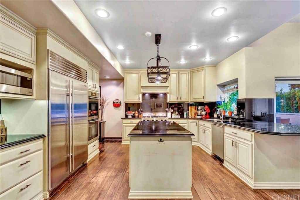 The beige cabinets and drawers of this kitchen have metal handles that coordinate the metal draping light apparatus over the dark ledge of the kitchen island that matches with the L-shape peninsula.