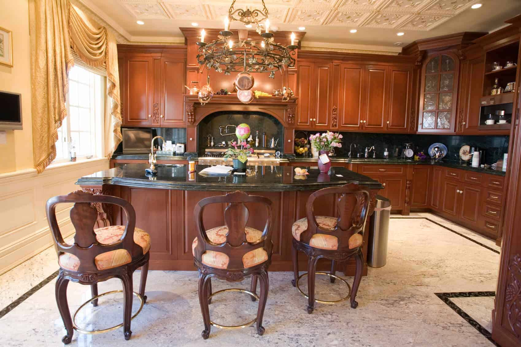 Dark cherry wood and darker marble countertops unify this kitchen, featuring expansive kitchen island lit by a stunning chandelier.