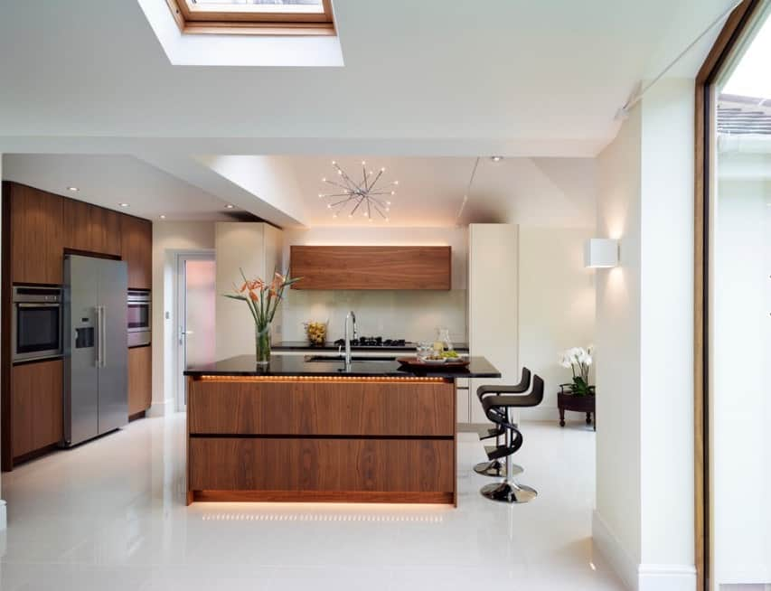 A kitchen island with a dark countertop and wooden base uncovers some implicit lighting that makes it all the more fascinating.