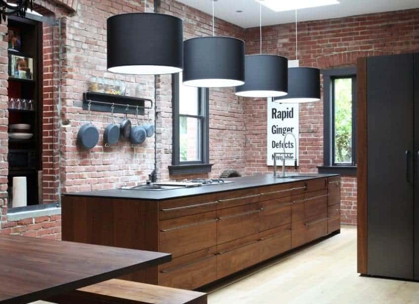 This kitchen features a black countertop island and a brick wall. It also has wooden cabinets and wooden dining tables.