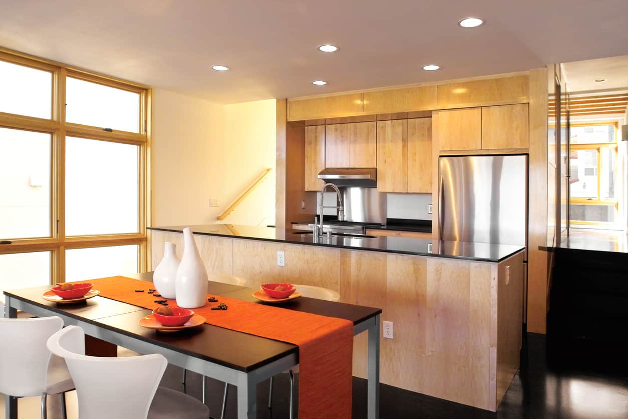 This kitchen features a small single divider with an island kitchen with a lot of light natural wood and stainless steel appliances.