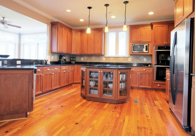 The warm cabinets in this kitchen supplement the wood flooring, while at the same time everything is adjusted by the black countertops and stainless steel appliances.
