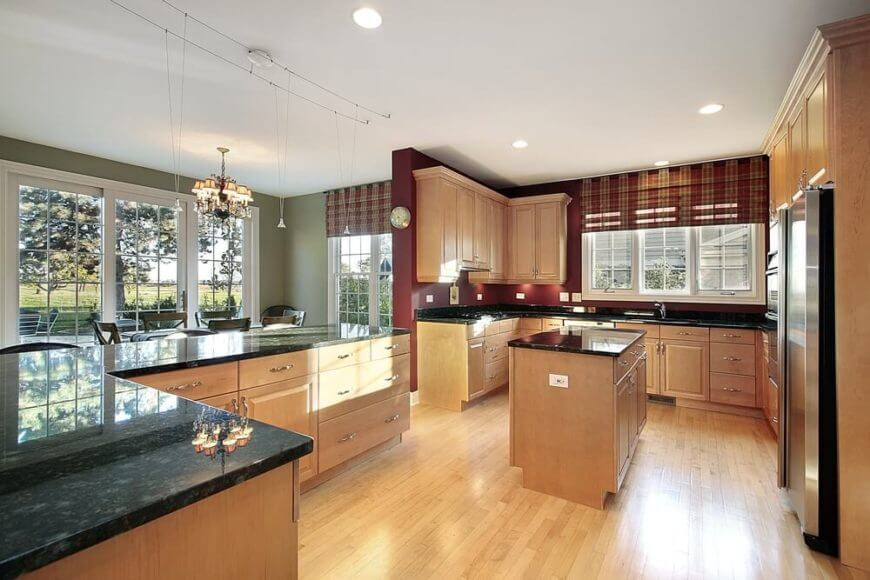 This kitchen features a light wood of these floors and cabinets balances the bold wall colors and dark countertops