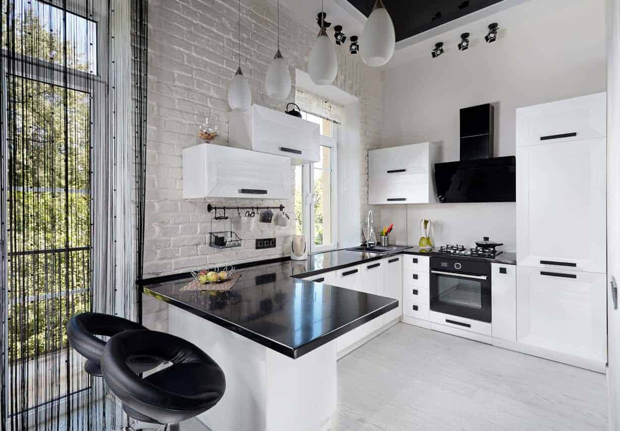 This modern black and white kitchen has a black countertop and white cabinetry that matches the tiled flooring.