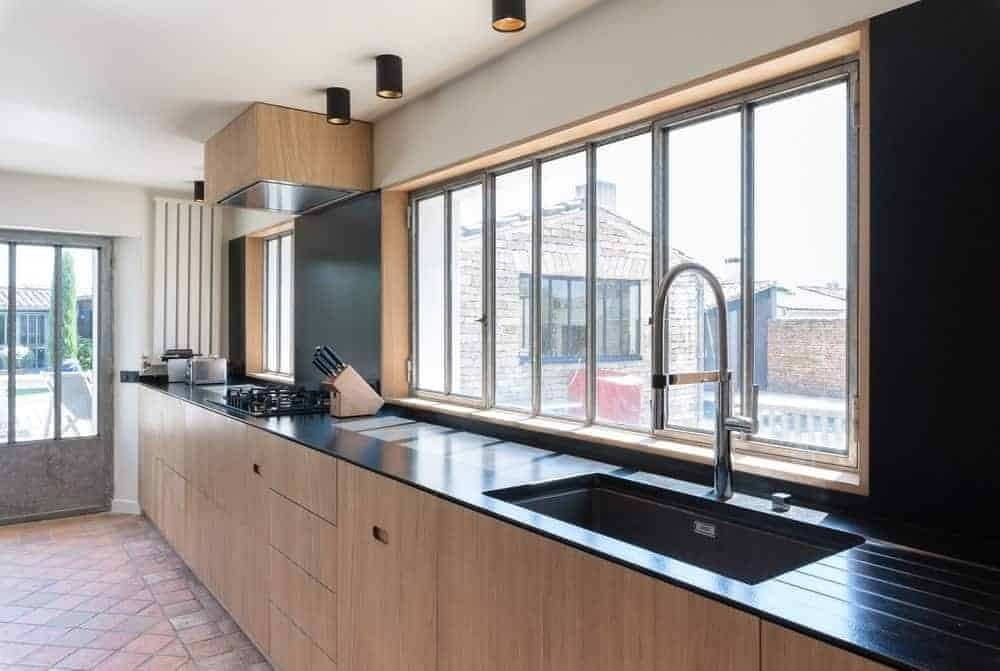 This classy kitchen with black countertops with gooseneck faucet and black backsplash along with glass windows.
