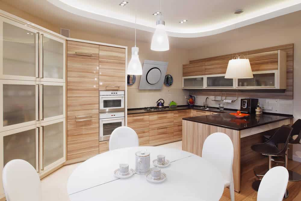 This kitchen shares with dining area with a white dining table with white chairs. The kitchen features black countertops and wooden cabinets.