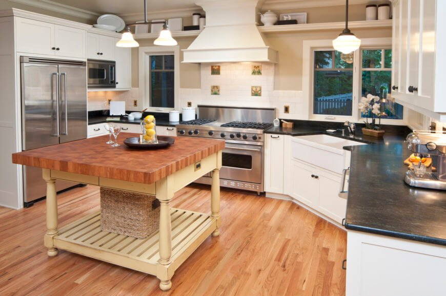 This kitchen features a wooden top kitchen island on the hardwood flooring and black countertops. It also has stainless steel appliances.