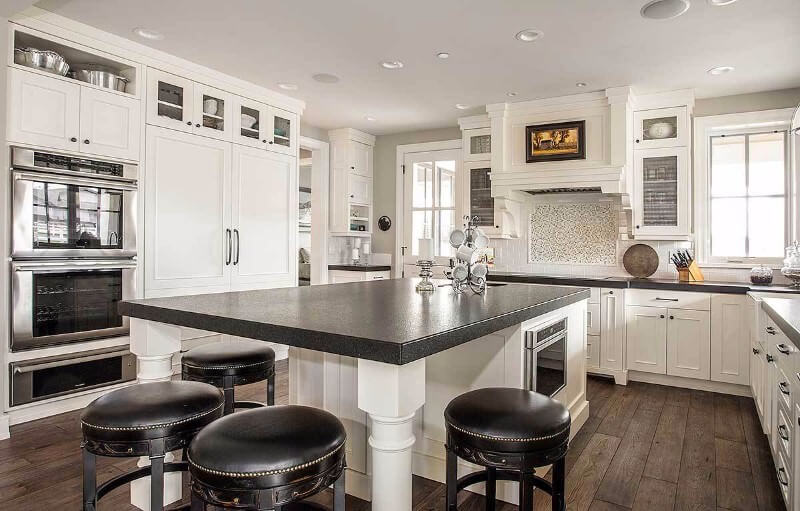 This white kitchen features dark countertops and dark island surface. The dark contrast continues with dark flooring and black round stool upholstery.