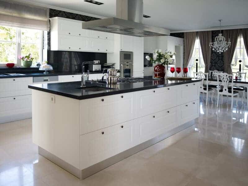 A kitchen of complexities holds this enormous island in black and white, loaded with expansive built-in storage andfull island range.