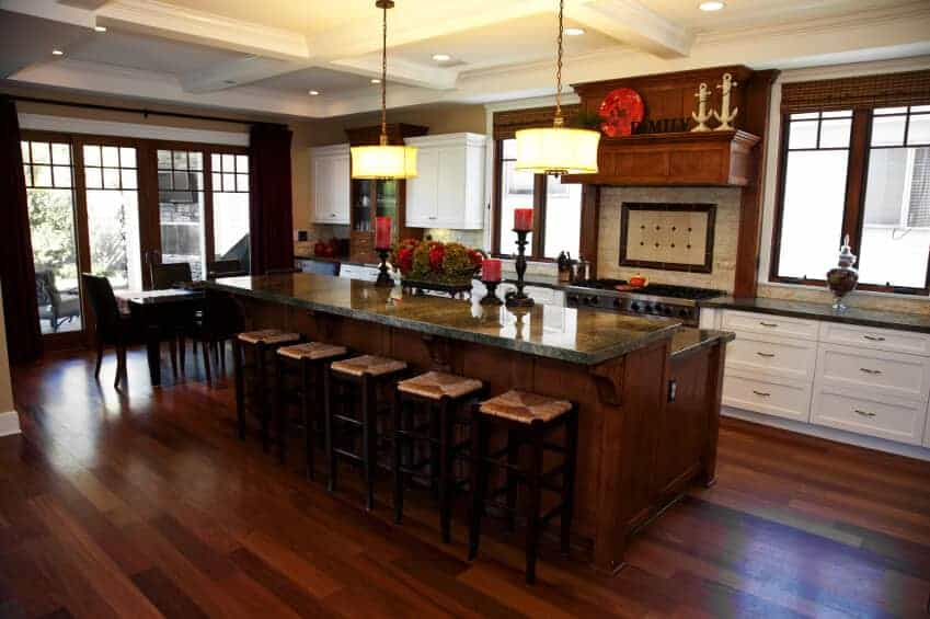 Rich dim wood tones all through this kitchen including a two-level island with thoroughly stocked bar seating and black marble countertops.