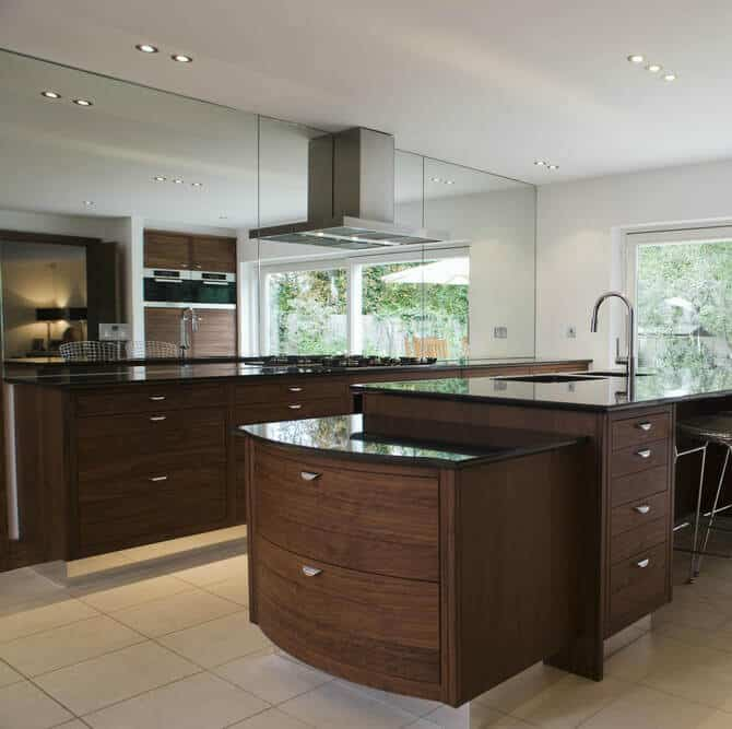 This kitchen with a two-tiered island adding contrast to a kitchen with warm natural wood and dark marble countertop.