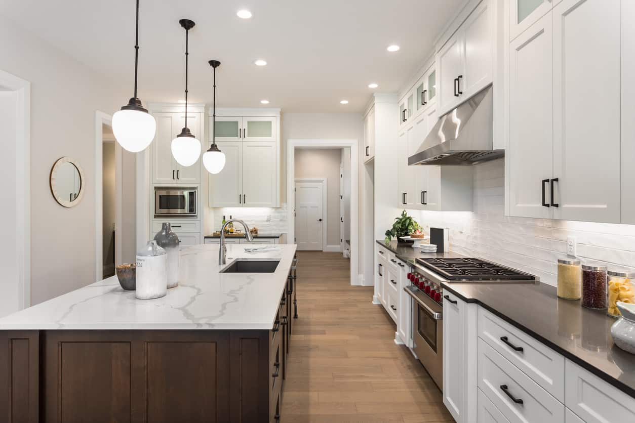 This kitchen with black countertop and white cabinets and drawers. It also has a white marble top kitchen island lightens by a pendant lights.
