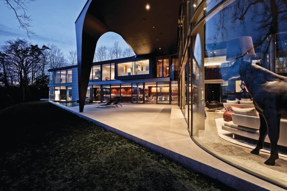 Night view of the rear patio with a pool in the Lake House designed by ARRCC.