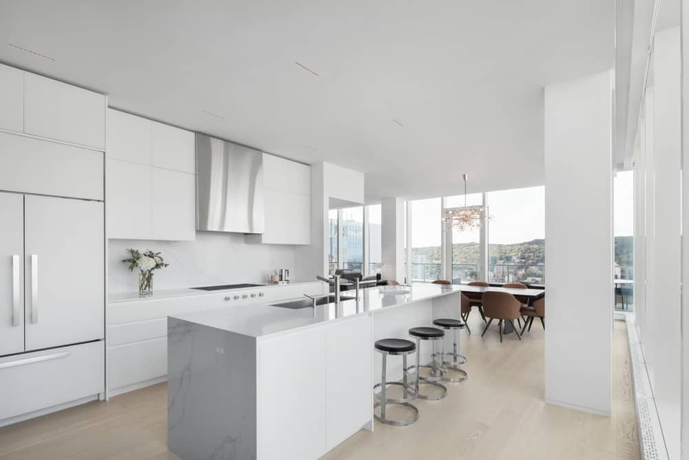 This modern white kitchen is enormous and well lit up by a lot of common light. The kitchen definitely exudes a minimalist design.