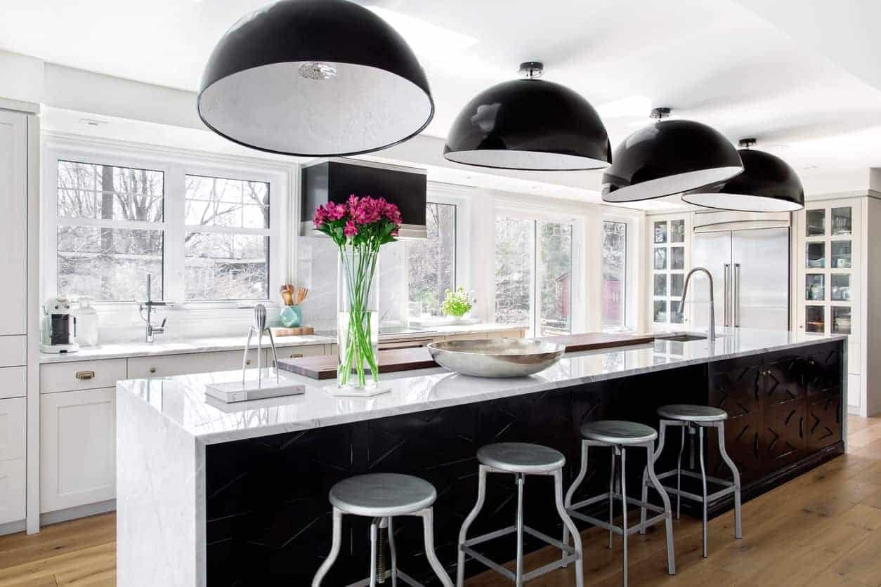 This white kitchen has a white marble top center island with a bar stool lit by stunning pendant lights.