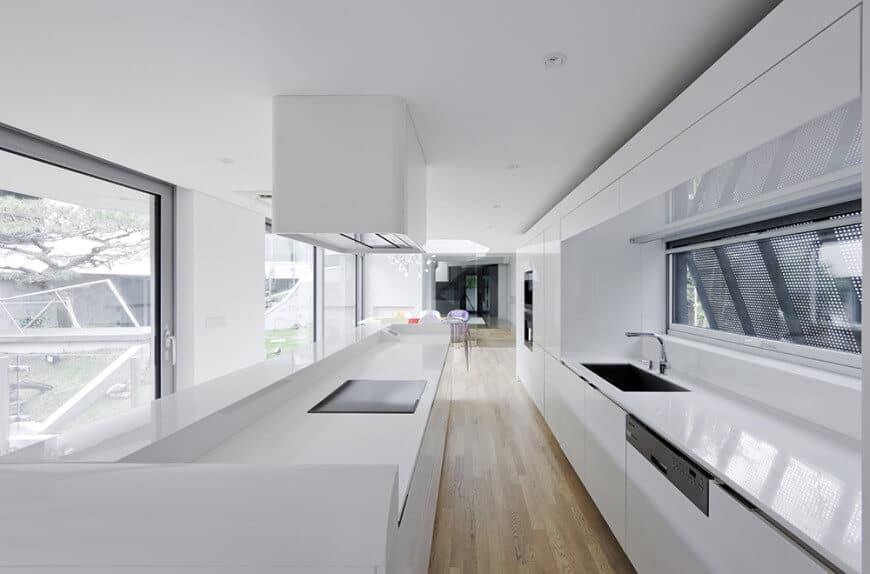 This long narrow kitchen design with a white countertop that matches white walls and ceiling with recessed lights.