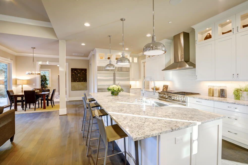 This kitchen features a double-wide stainless steel fridge looks mighty nice along with the matching chrome pendant lights in this large, luxury l-shaped kitchen.