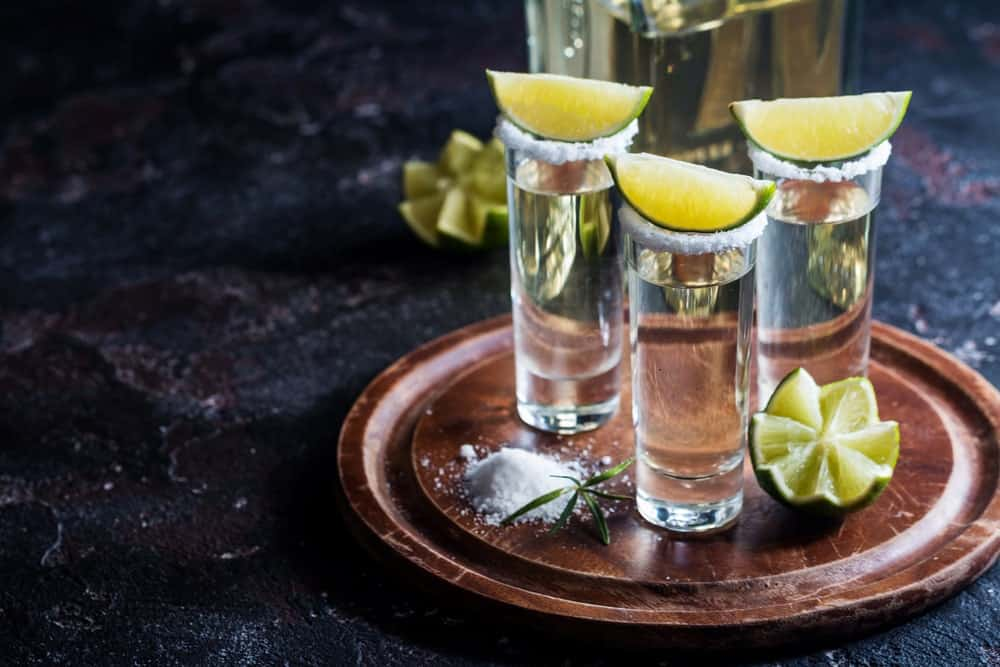 A serving of three glass of tequila with lime and salt.