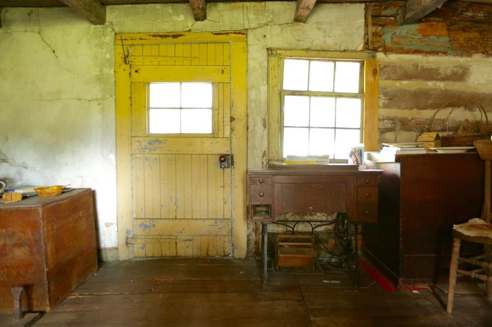There are a number of antique wooden furniture inside the home that are complemented by the rustic walls, hardwood flooring and the wooden door with a glass panel window. Images courtesy of Toptenrealestatedeals.com.