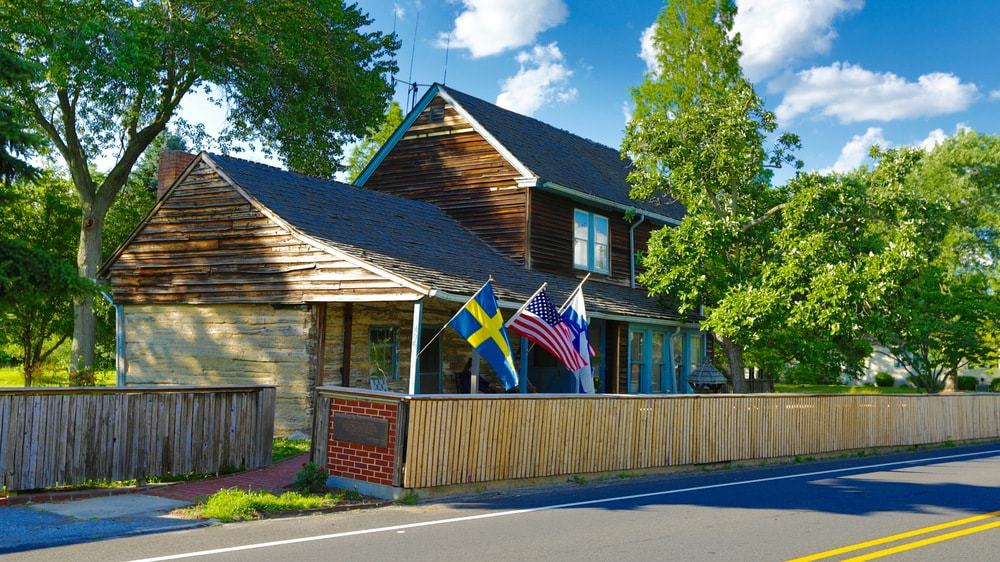 The historic log cabin has rich wooden exteriors and has a wooden fencing separating it from the road. The earthy tones of the house are complemented by the tall trees. Images courtesy of Toptenrealestatedeals.com.