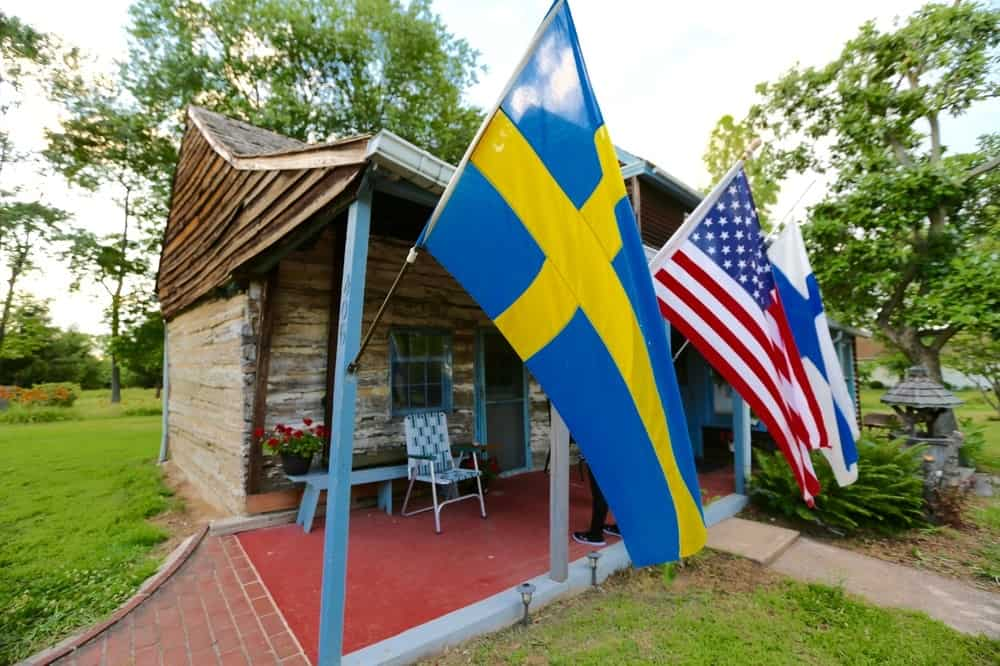 This is a closer look at the front of the house with Finnish and American flags attached to thin blue posts that support the wooden ceiling of the front porch. Images courtesy of Toptenrealestatedeals.com.