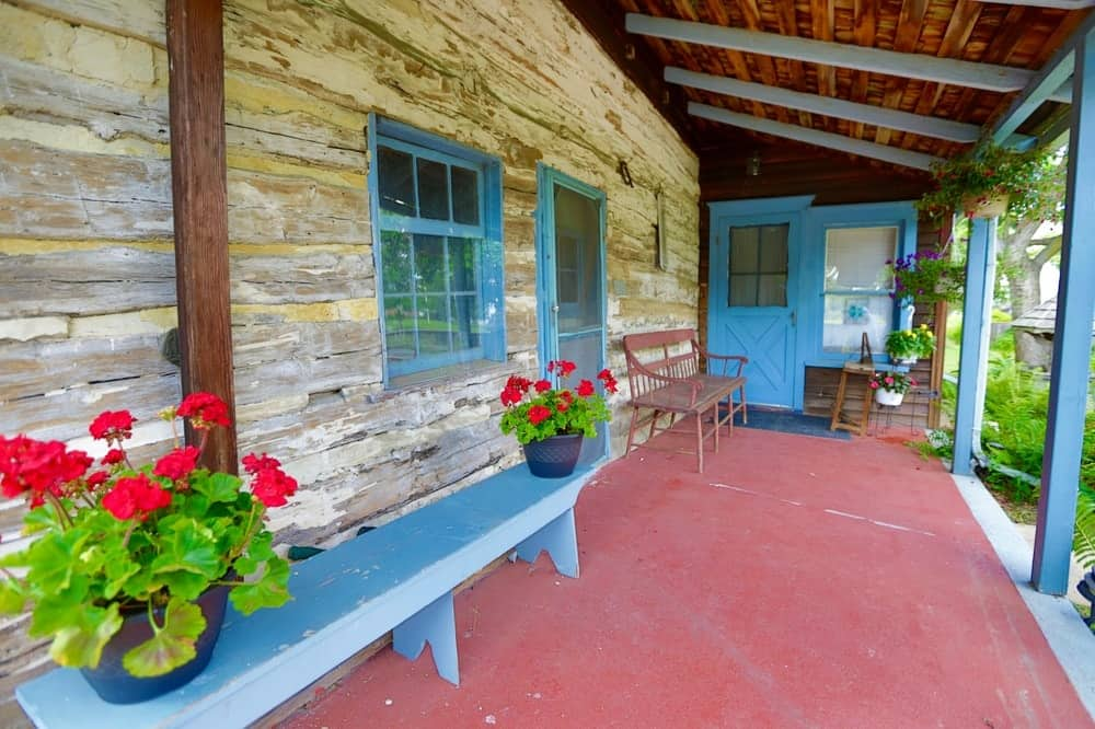 This is the charming front porch that welcomes you with terracotta flooring and lovely wooden exterior walls that are complemented by blue elements. Images courtesy of Toptenrealestatedeals.com.